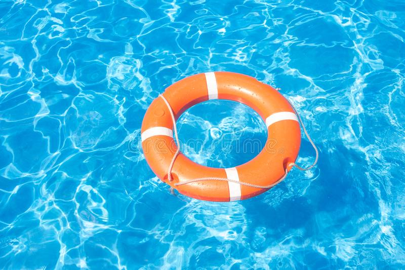 Orange lifebuoy on a background of blue water pool royalty free stock images