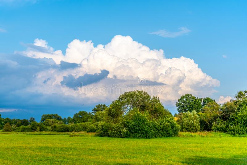 Before summer storm. Dramatic clouds coming in green and sunny landscape stock photography