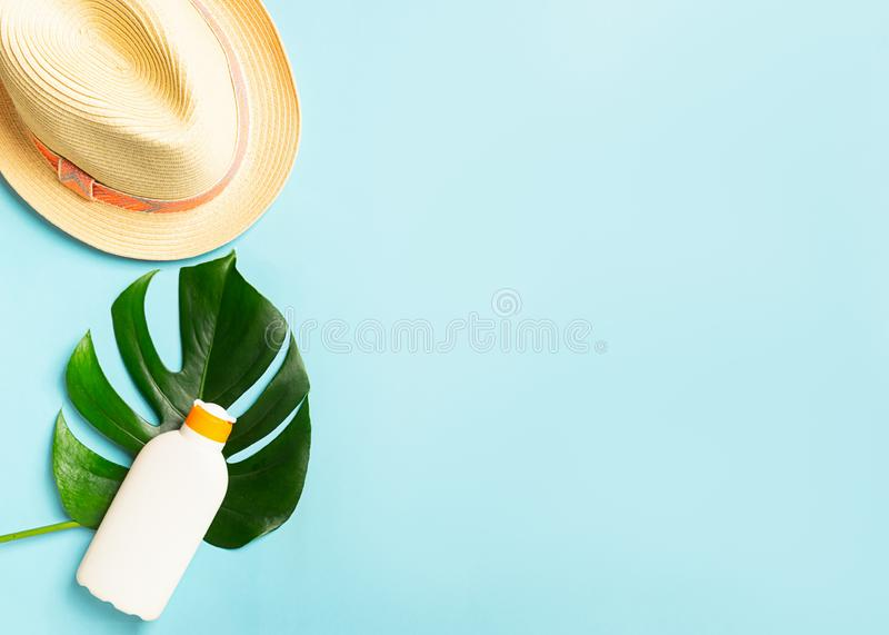 Summer straw hat sunscreen green leaf of an exotic monstera plant bright blue background. The concept of summer holidays stock photos