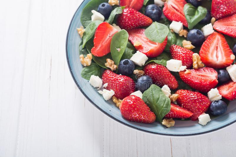 Summer Strawberry salad with spinach , cheese , nuts and blueberry royalty free stock images