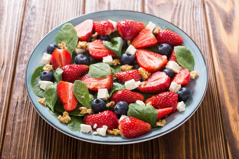 Summer Strawberry salad with spinach , cheese , nuts and blueberry royalty free stock photography