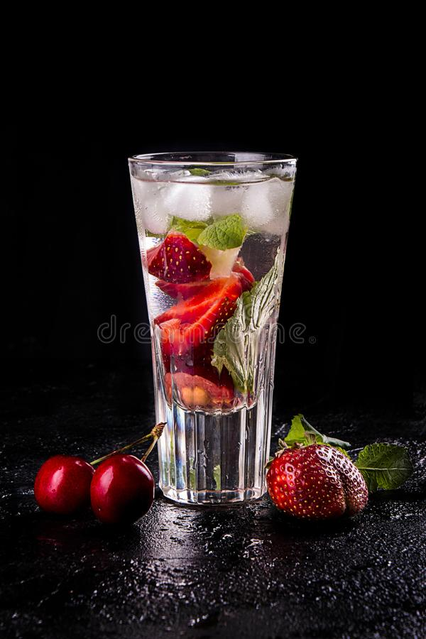 Summer strawberry sweet cherry cocktail ice cold drink in glasses on black background stock images