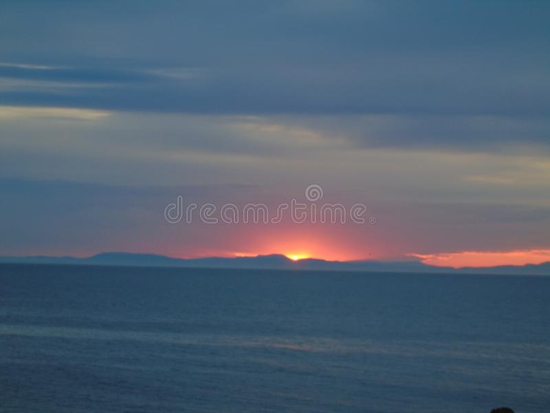 Sun sets on the Black Isle. Summer sun sets behind the hills of the Black Isle over the Moray Firth. Fading reds mix with the evening blue of the sky and hills stock image