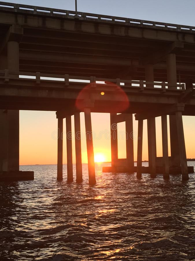 The summer sun sets beneath the bridges to Pensacola Beach. Wonderous last light of the setting sun, dance across wavelets beneath the Bob Sykes Bridge which stock photos