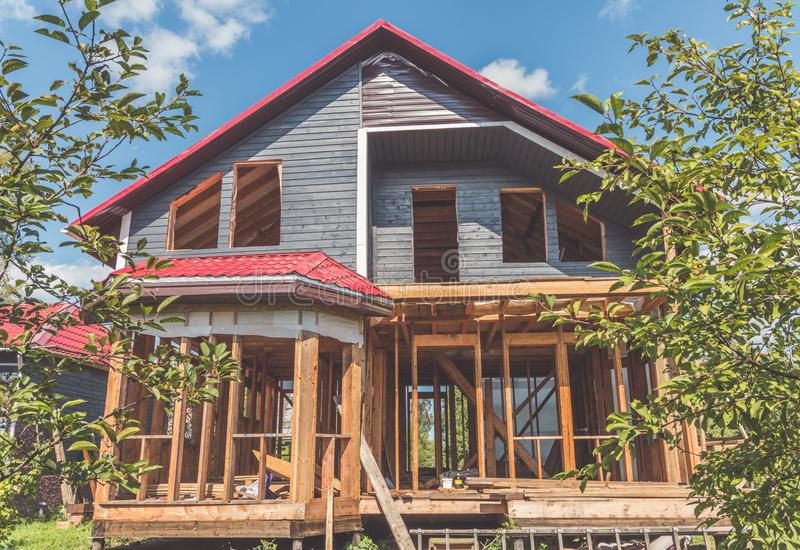 The summer Sunny day frame wooden house with a roof made of meta stock photo