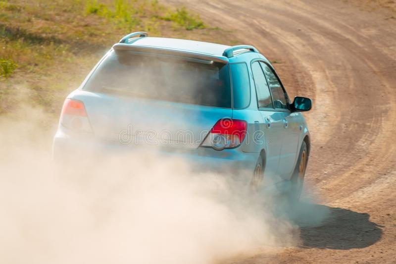 Rear View of a Blue Car on a Dusty Road royalty free stock images