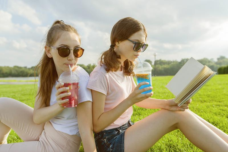 Summer sunny day, two girlfriends teenagers sit on green lawn, drink cocktails, talk, read book, laugh, have fun. stock image