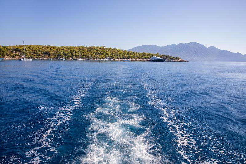 Summer sunny day yachting off the coast of the Agistri island - leaving Aponisos bay, Saronic Gulf, Greece. Horizontal. Photo taken from the yacht stock photo