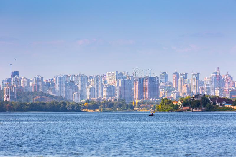 Summer sunny hot evening. Modern residential areas southern suburbs and midtown on hills in Kyiv on the right bank of the Dnipro. River. Fishermen on boats on royalty free stock image