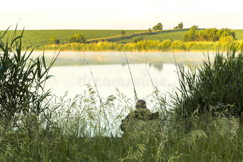 Summer sunny landscape. Morning, dawn on the lake. A fisherman s stock image