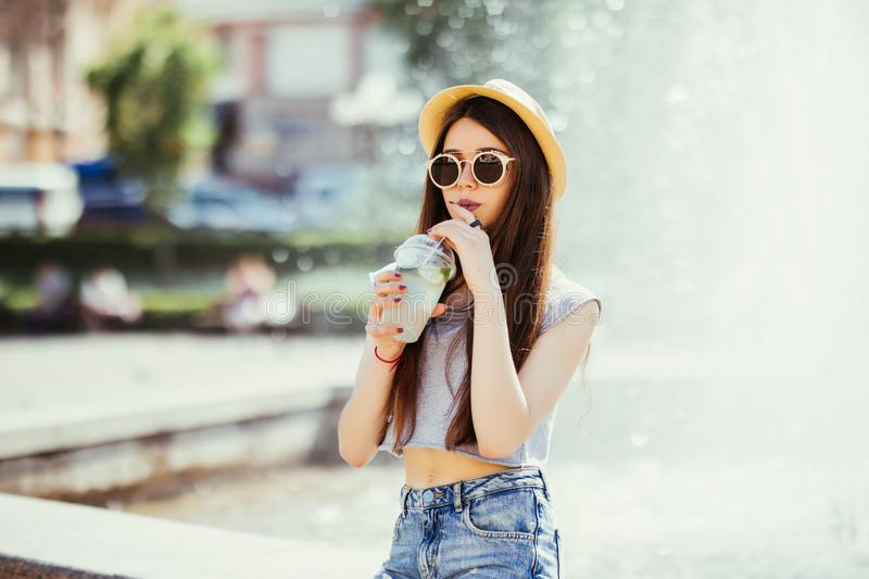 Summer sunny lifestyle fashion portrait of young stylish hipster woman walking on the street, wearing cute trendy outfit, drinking royalty free stock photo