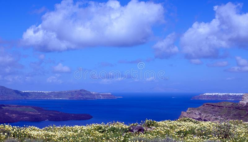 Summer sunny morning on the island of Santorini, Greece. Blue sea, blue sky with clouds against the background of the island. royalty free stock images