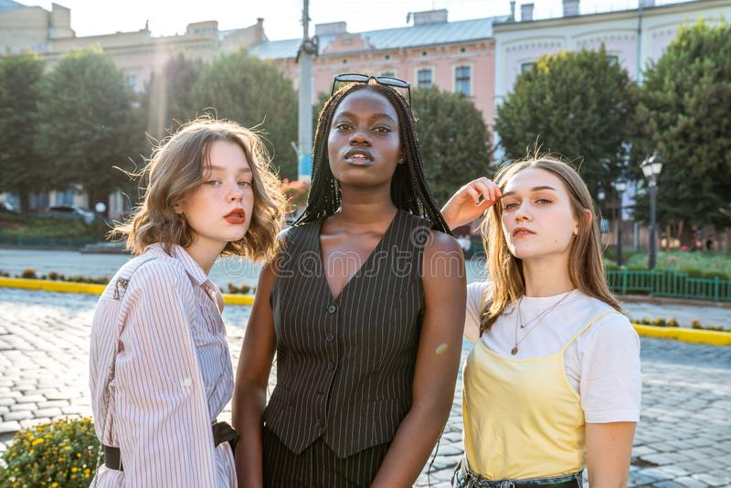 Summer sunny street style fashion portrait of multi ethnic girls posing among old city center. Outdoor photo stock photos