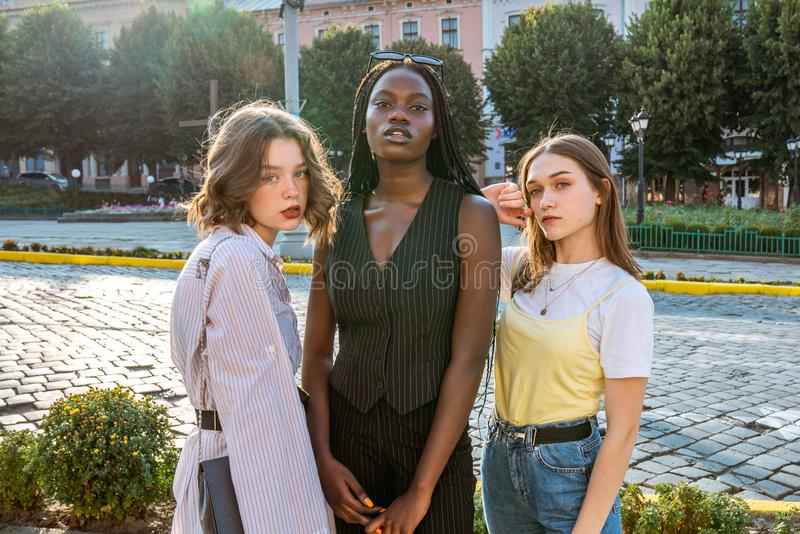 Summer sunny street style fashion portrait of multi ethnic girls posing among old city center. Outdoor photo royalty free stock photography