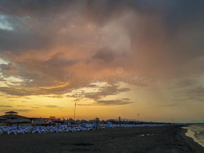 Summer sunrise with clouds and soft rain during early morning on the beach with chairs next to the sea. Early morning stock image