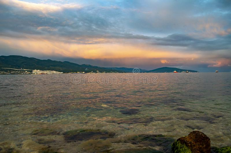 Summer sunset at black sea. Stones, water, mountains royalty free stock images