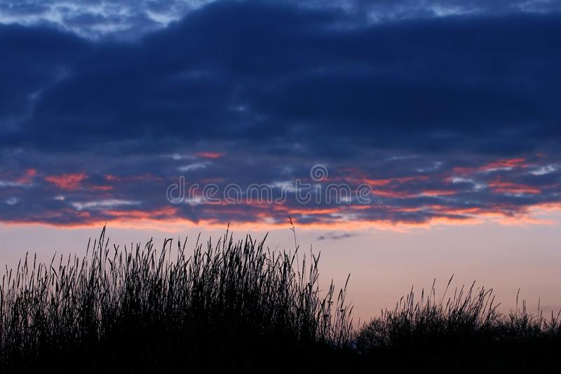 Stormy clouds on sunset sky. Summer sunset with dramatic clouds royalty free stock images