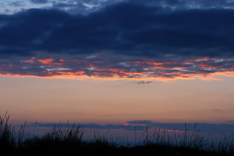 Stormy clouds on sunset sky. Summer sunset with dramatic clouds royalty free stock photos