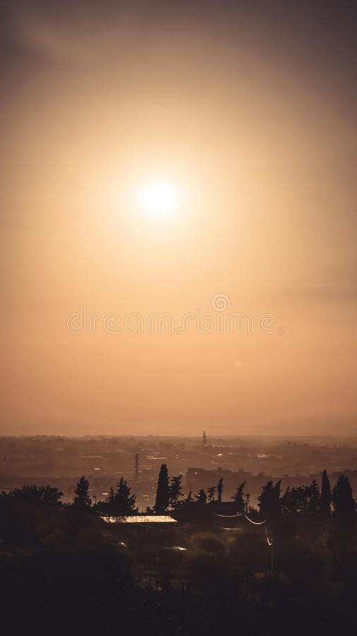 Summer Sunsets in algeria. Silhouette of trees and branch and buildings of blida city under an orange sky sunset of 2017 summer royalty free stock photography