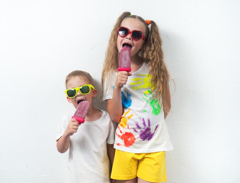 Summer sweets for children: Children boy and girl in sunglasses and colored T-shirts eating pink home ice cream on white royalty free stock photos