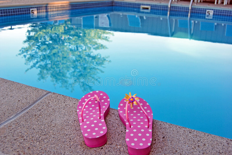 polka dot flip-flops by swimming pool stock images