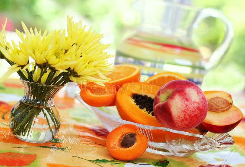 Summer table. Bright, colorful summer table with tropical fruits and flowers royalty free stock photos