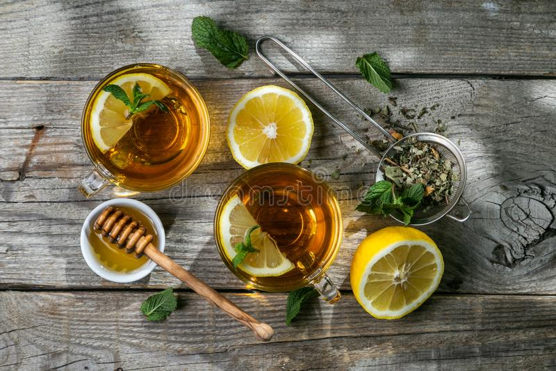 Summer tea - tea cups on rustic wood background with leaves shades - garden royalty free stock photography