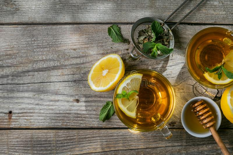 Summer tea - tea cups on rustic wood background with leaves shades - garden royalty free stock images