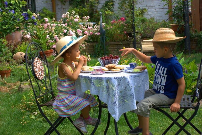 Summer tea-time. 2 children enjoying 'grown up' teatime in sunny garden stock images
