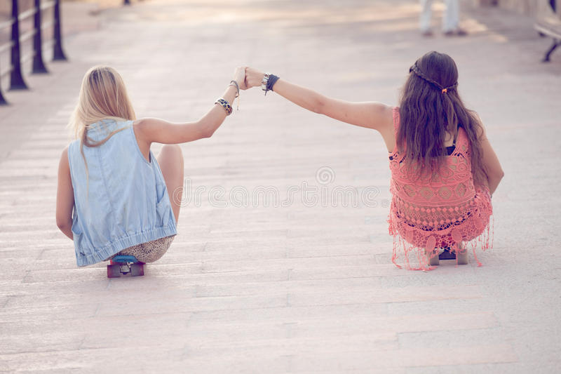 Summer teens girls sitting on skateboards royalty free stock images