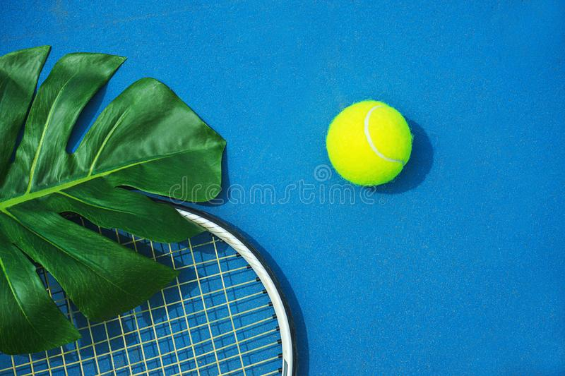 Summer tennis concept with green monstera leaf and ball, racquet on hard tennis court. stock image