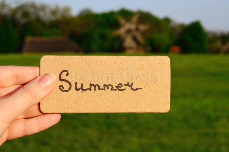 Summer text on a card. Girl holding card in a field with windmi stock photography