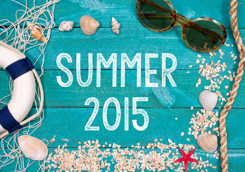 Summer 2015. Text 'Summer 2015' painted in uppercase white letters on green wooden boards with sun glasses, rope, sea shells, sand, star fish and lifebuoy along stock images