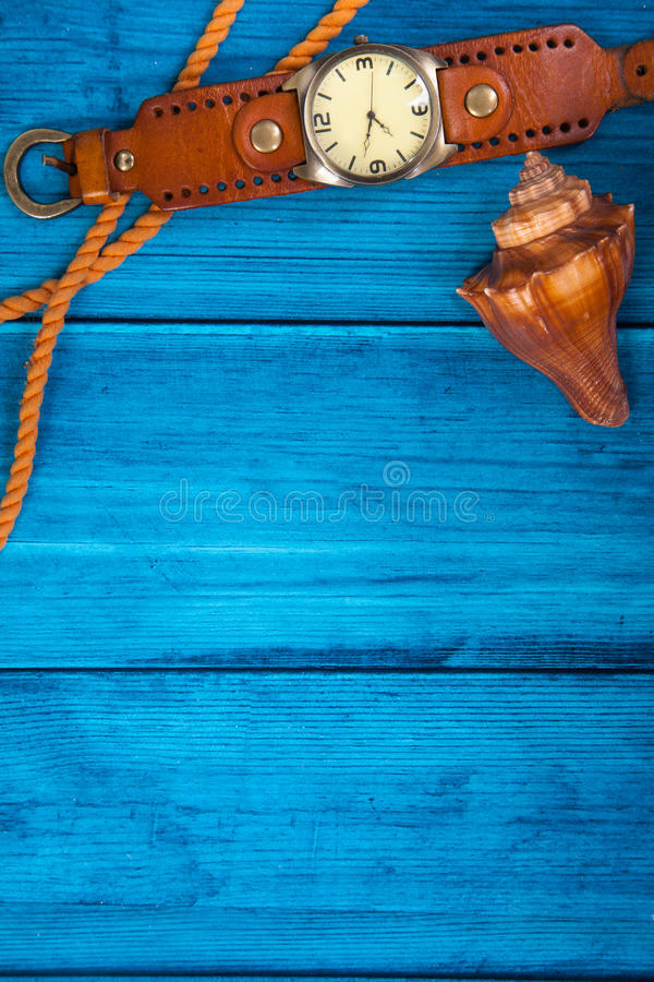 Summer theme blue background with space for advertising and maritime theme. (seashells, starfish, sea knots, anchor) and watches royalty free stock photography