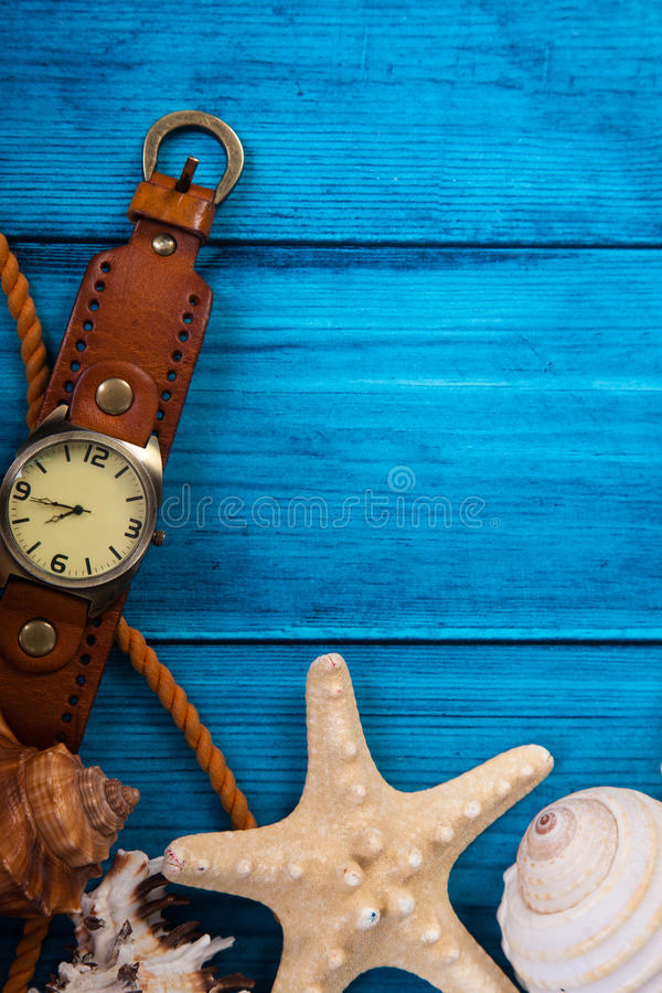 Summer theme blue background with space for advertising and maritime theme. (seashells, starfish, sea knots, anchor) and watches stock photos