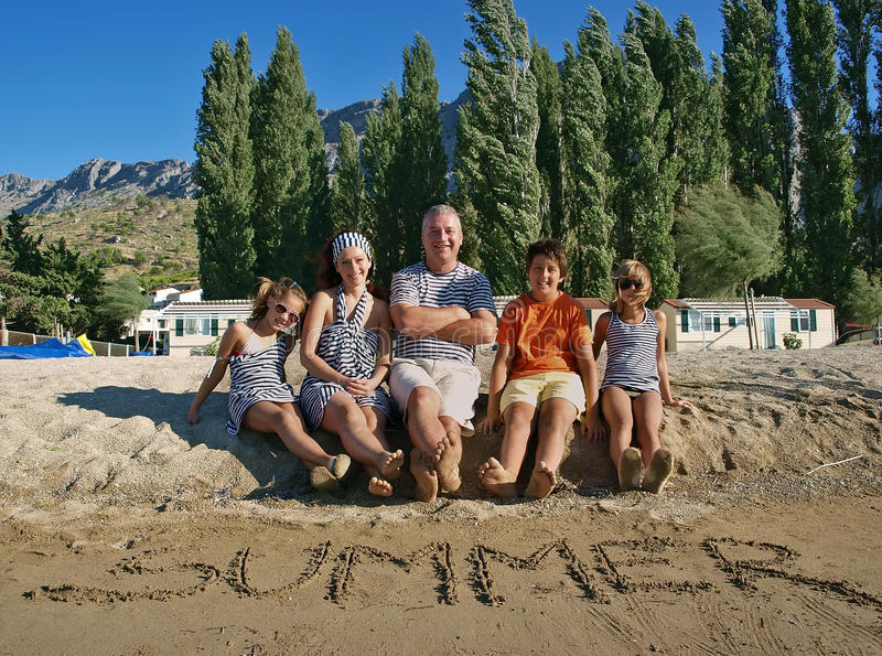 Summer time. Summer write on the sandy beach and a happy smiling family spending holidays in Croatia sandy beach (Dalmatia stock images