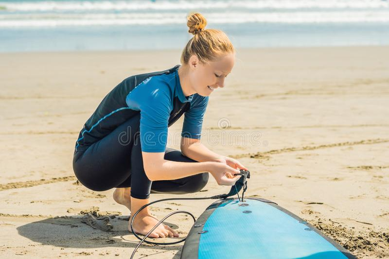 Summer time and active rest concept. Young surfer woman beginner. Fastens leash across leg, going to surf on big barral waves on ocean, dresseed in boardies royalty free stock images