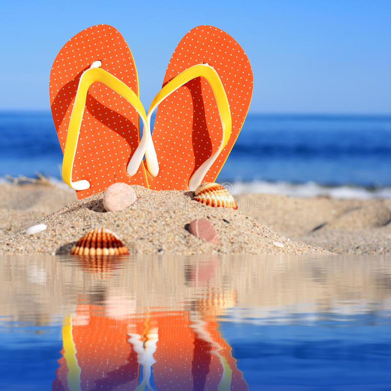 Summer time. Baby and flip-flops on the beach royalty free stock photos