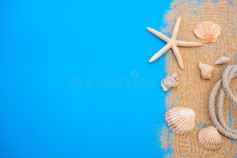 Summer time concept with sea shells and starfish on a blue wooden background and sand royalty free stock photo