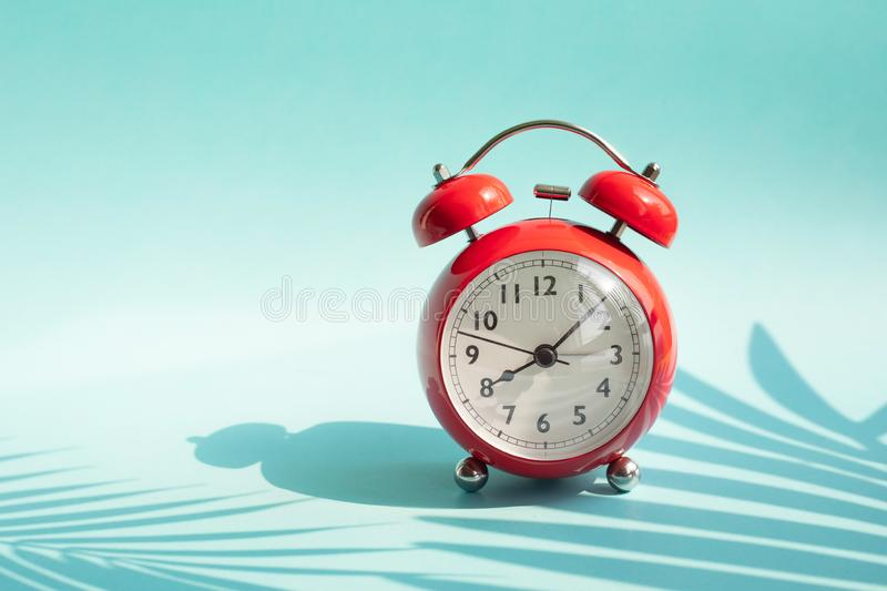 Summer time concepts idea with alarm clock and tropical leaf shadow on colorful background.holiday decoration stock images