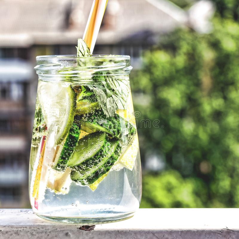 Detox drink from cucumber, lemon and mint on the background of a modern city. Summer time stock image