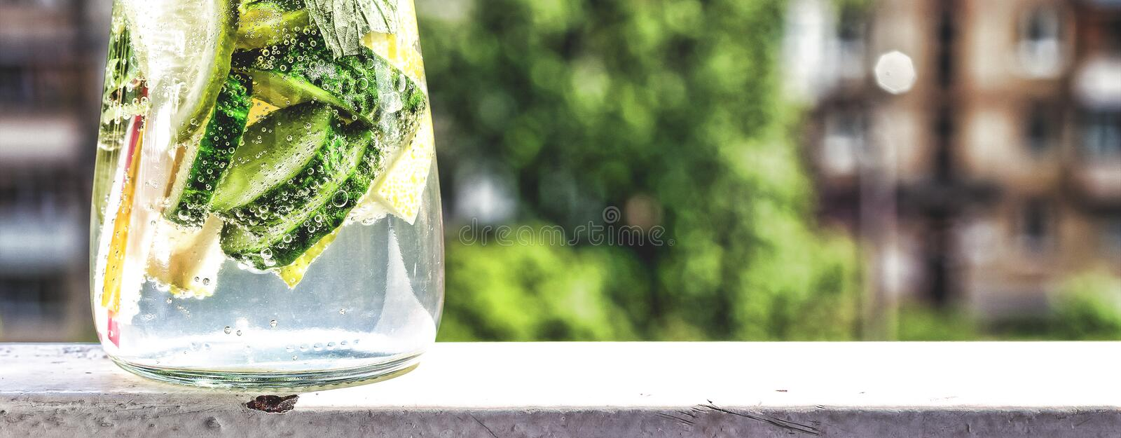 Detox drink from cucumber, lemon and mint on the background of a modern city. Summer time royalty free stock images