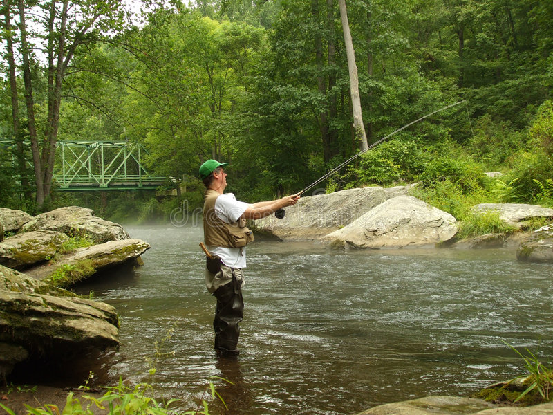 Summer Time Fishing. Photo of man fishing the deep pools below Falls Road bridge on the Gunpowder river for trout during summer. The Gunpowder is one of Maryland royalty free stock photography