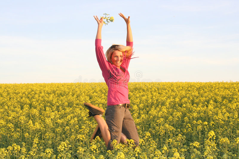 Summer time - Jump Woman. A beautiful young jumping woman and yellow flowers stock images