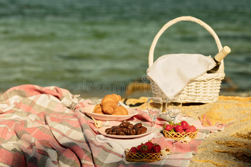 Summer time at the sea. Romantic picnic on the beach - wine, strawberries and sweets. royalty free stock photography