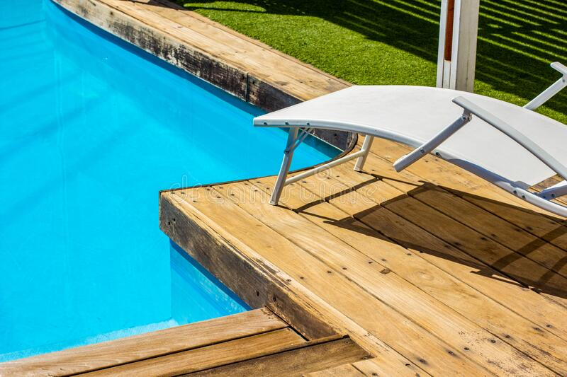 Summer time vacation season swimming pool side motel apartments back yard relaxation space lounge furniture in sunny weather day stock images