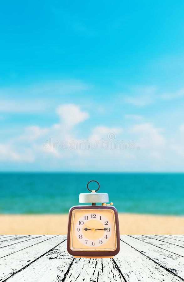 Summer Time, Vintage clock put on wooden with Blurred image. Of peaceful sea background stock photos