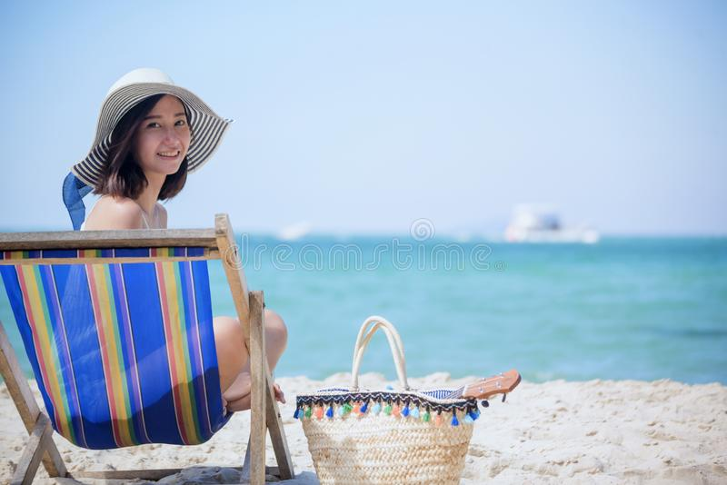 Summer time woman vacation on the beach. Cheerful woman wear summer dress and straw hats sitting on the beach look at sea. Time to stock photos