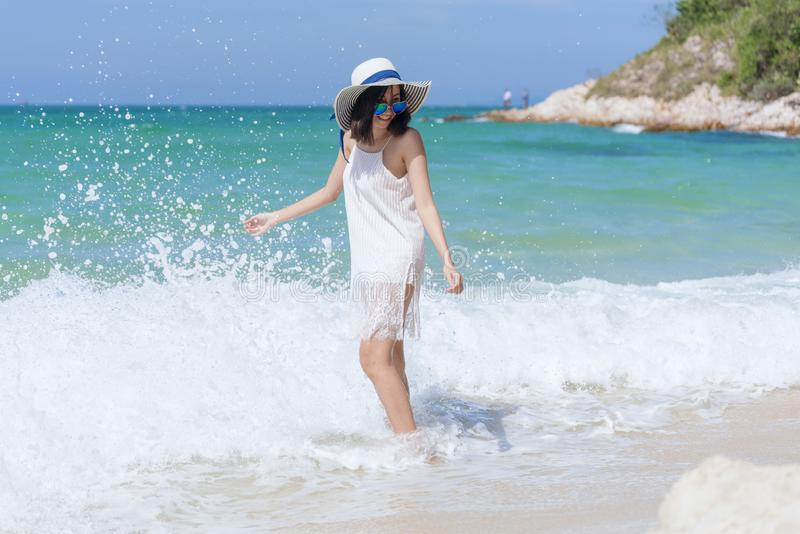 Summer time woman vacation on the beach. Cheerful woman wear summer dress and straw hats sitting on the beach look at sea. Time to royalty free stock images