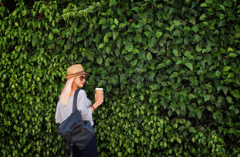 Summer time. Young girl with paper cup of coffee, light pink hair, straw hat and backpack on green wall background. royalty free stock images